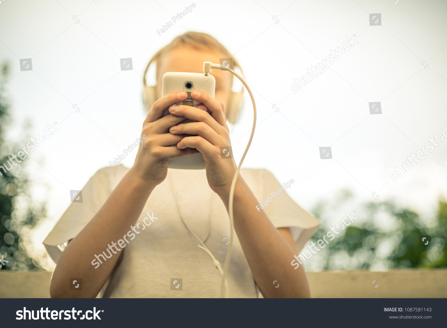 Young boy alone listening music with smartphone pre teen alone play with phone in hand