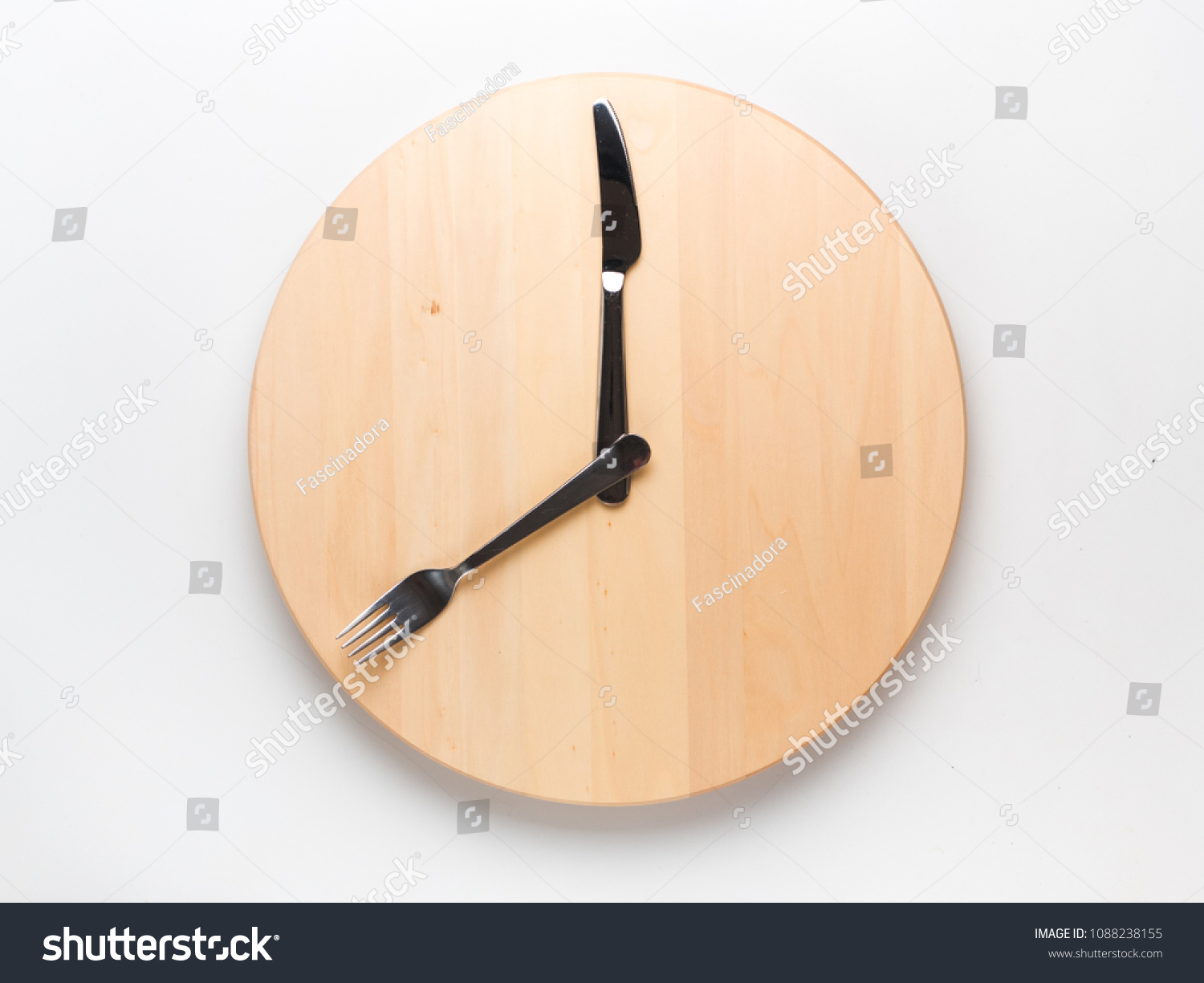 Intermittent fasting and skip breakfast concept - empty wooden round tray or trencher with cutlery as clock hands on white background. Eight hour feeding window concept or breakfast time concept #1088238155