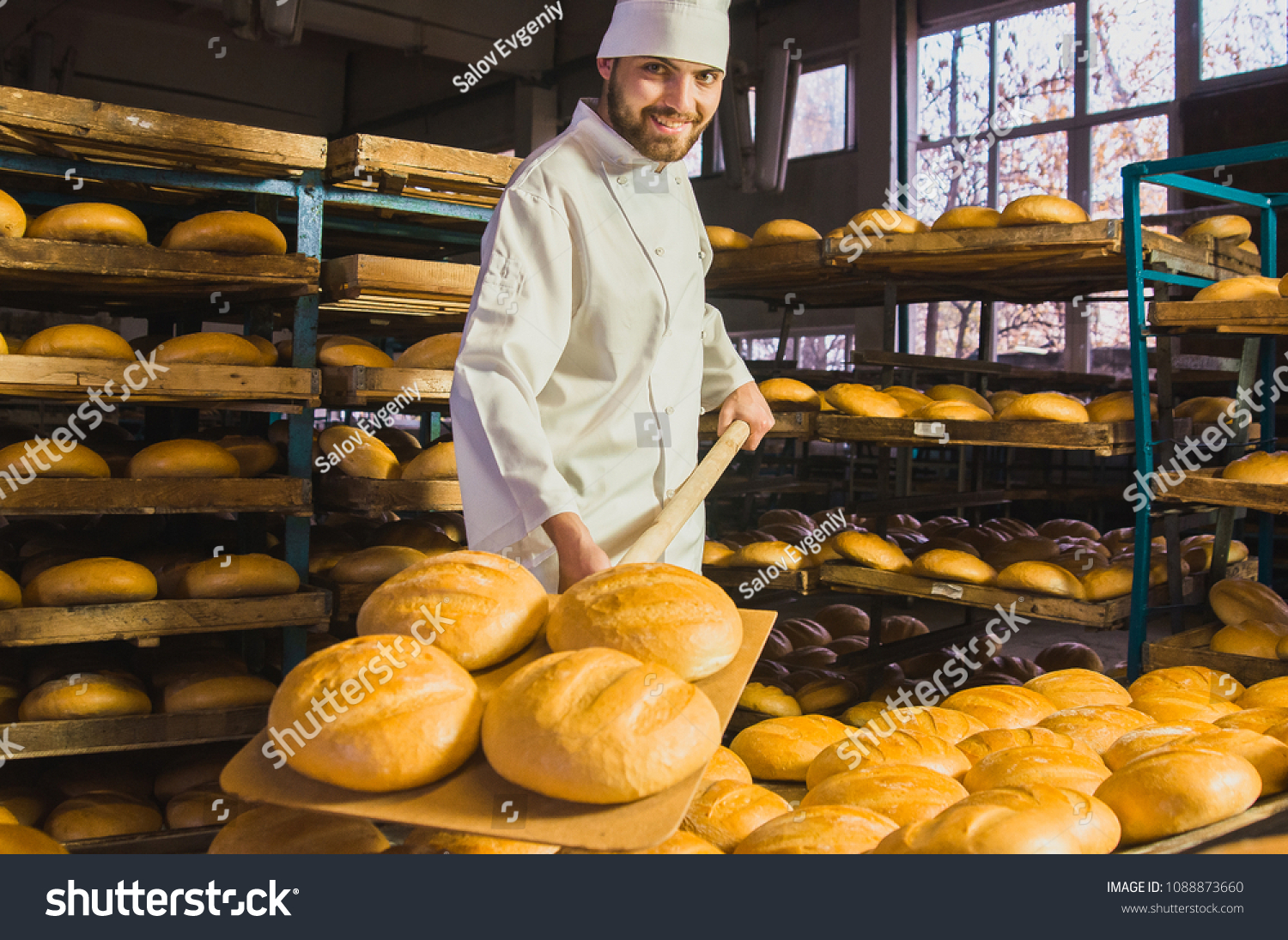 Baker. A young handsome bakery worker on the background of bread, takes bread from a stove with a wooden shovel. Industrial production of bakery products. a man in the baker's special clothing. Bakery #1088873660