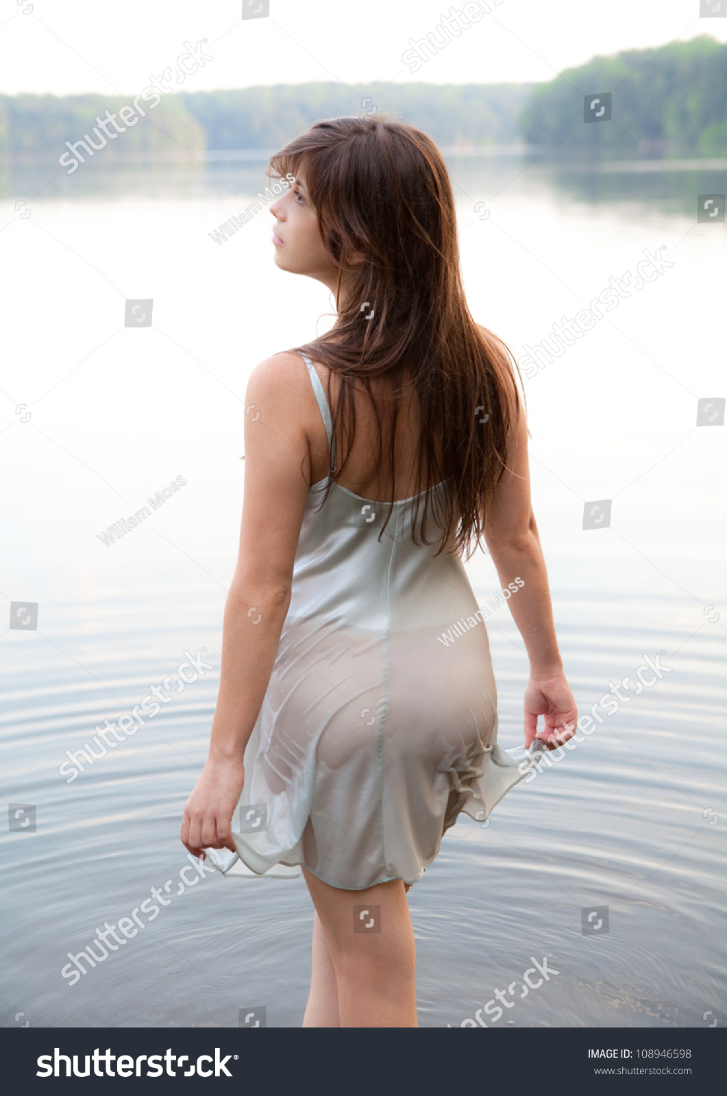 ...http://www.shutterstock.com/pic-108946598/stock-photo-woman-wading-in-lake-with-wet-dress.html.