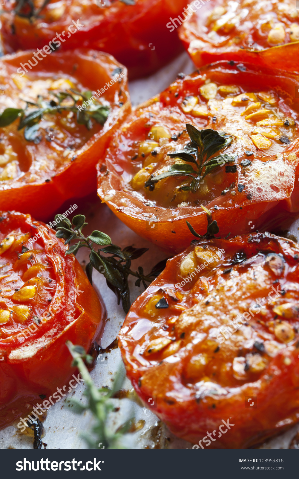 Roasted cherry tomatoes with herbs, on a baking tray straight from the ...