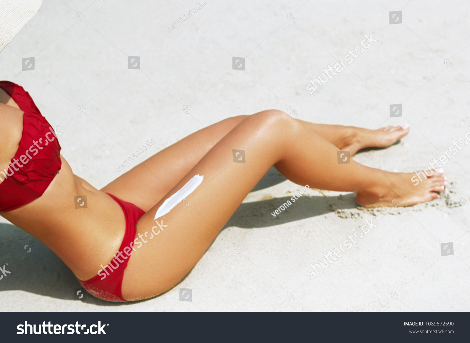 Sunscreen sun drawing lotion on suntan legs relaxing tanning on tropical beach holiday. Women lower body lying with sunblock cream  #1089672590