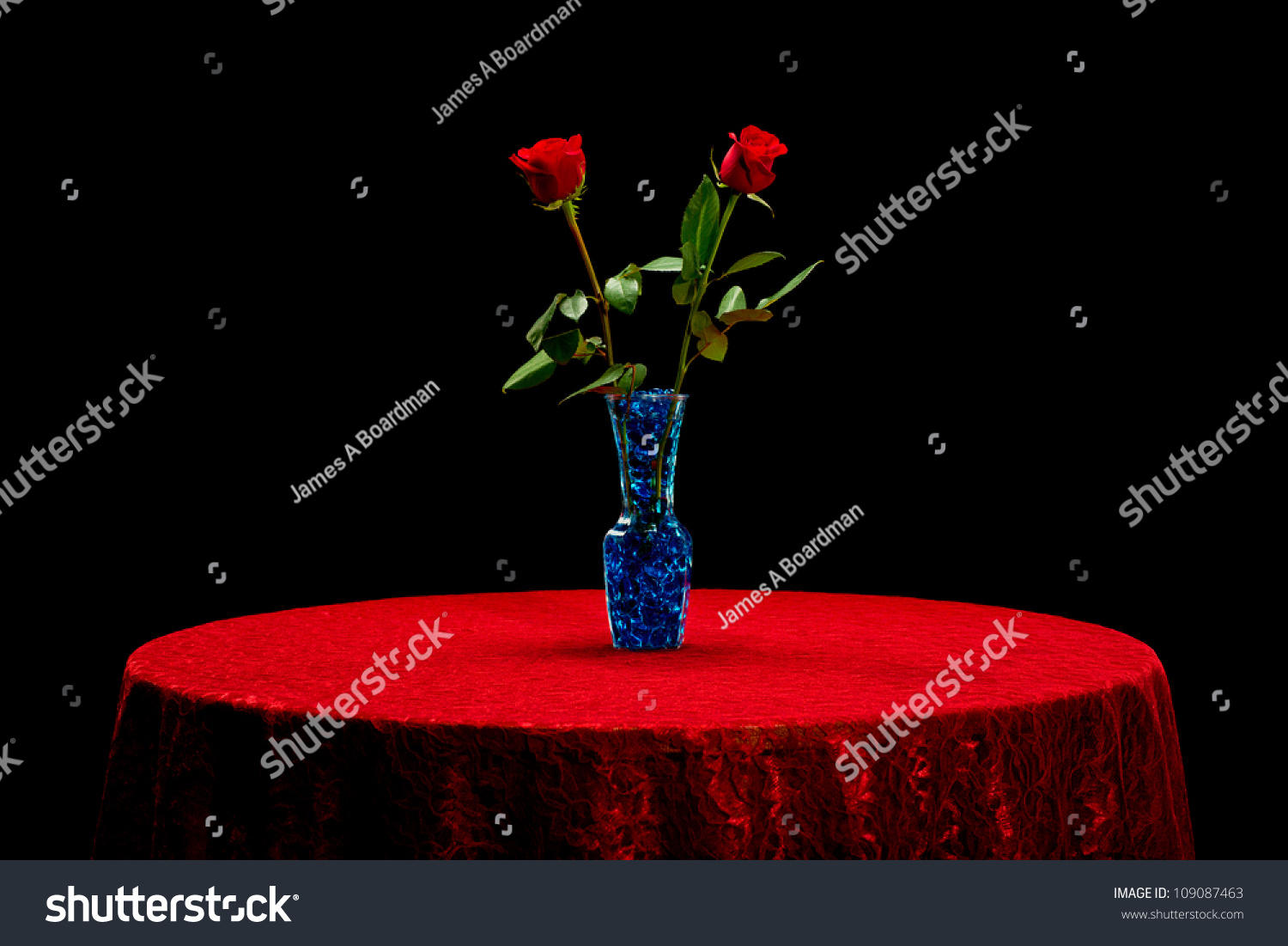 Two Red Roses In A Vase With Blue Stones On A Red Lace Tablecloth Isolated  On