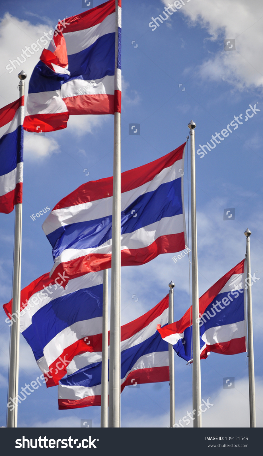 Thai flags waving on a sunny day under a blue sky with some clouds