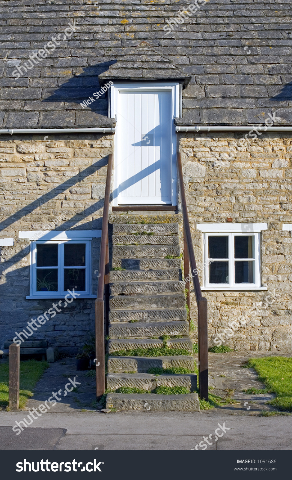 Traditional stone clad house with stone steps leading to the road on a sunny day in corfe - The shutter clad house ...