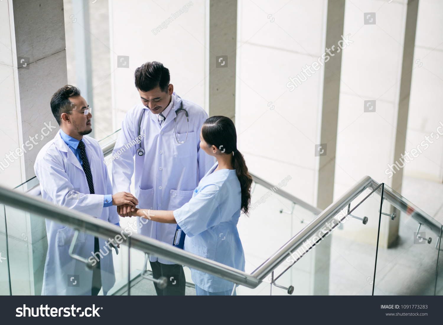 Cheerful Doctors Stacking Hands Express Unity Stock Photo