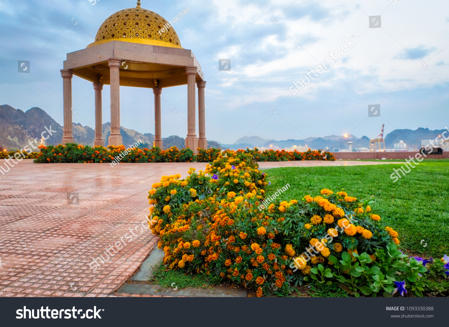 A line of flowers leading to the golden gazebo dome in the park. Shot from Muscat, Oman.