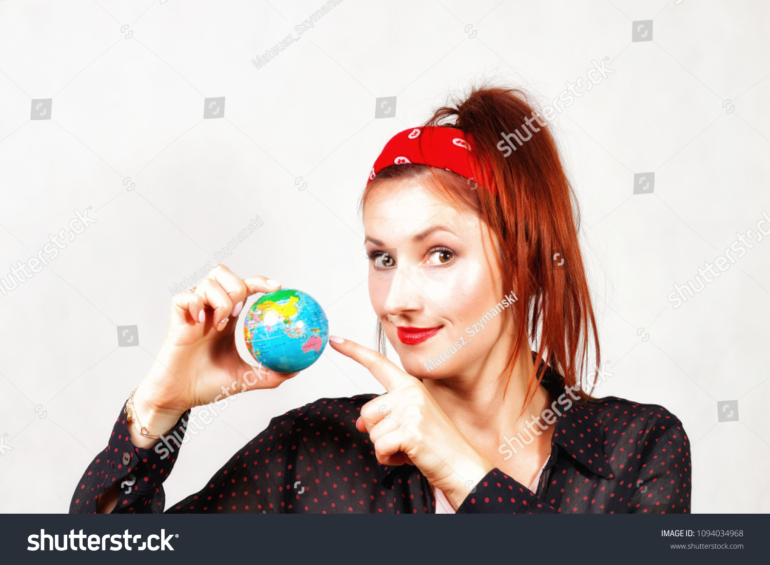 Young caucasian happy redhead pin up girl with red lips and bandana showing  little earth symbol