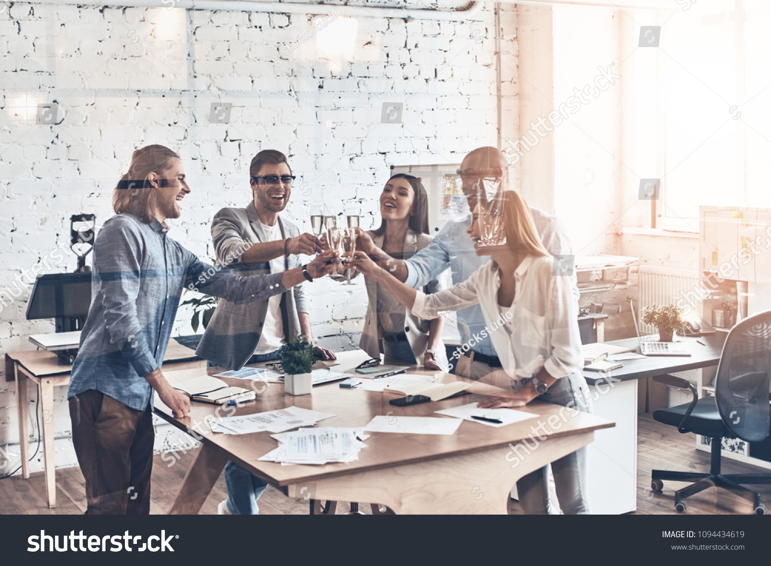 Toasting their success. Group of young business people toasting each other and smiling while standing behind the glass wall in the board room #1094434619