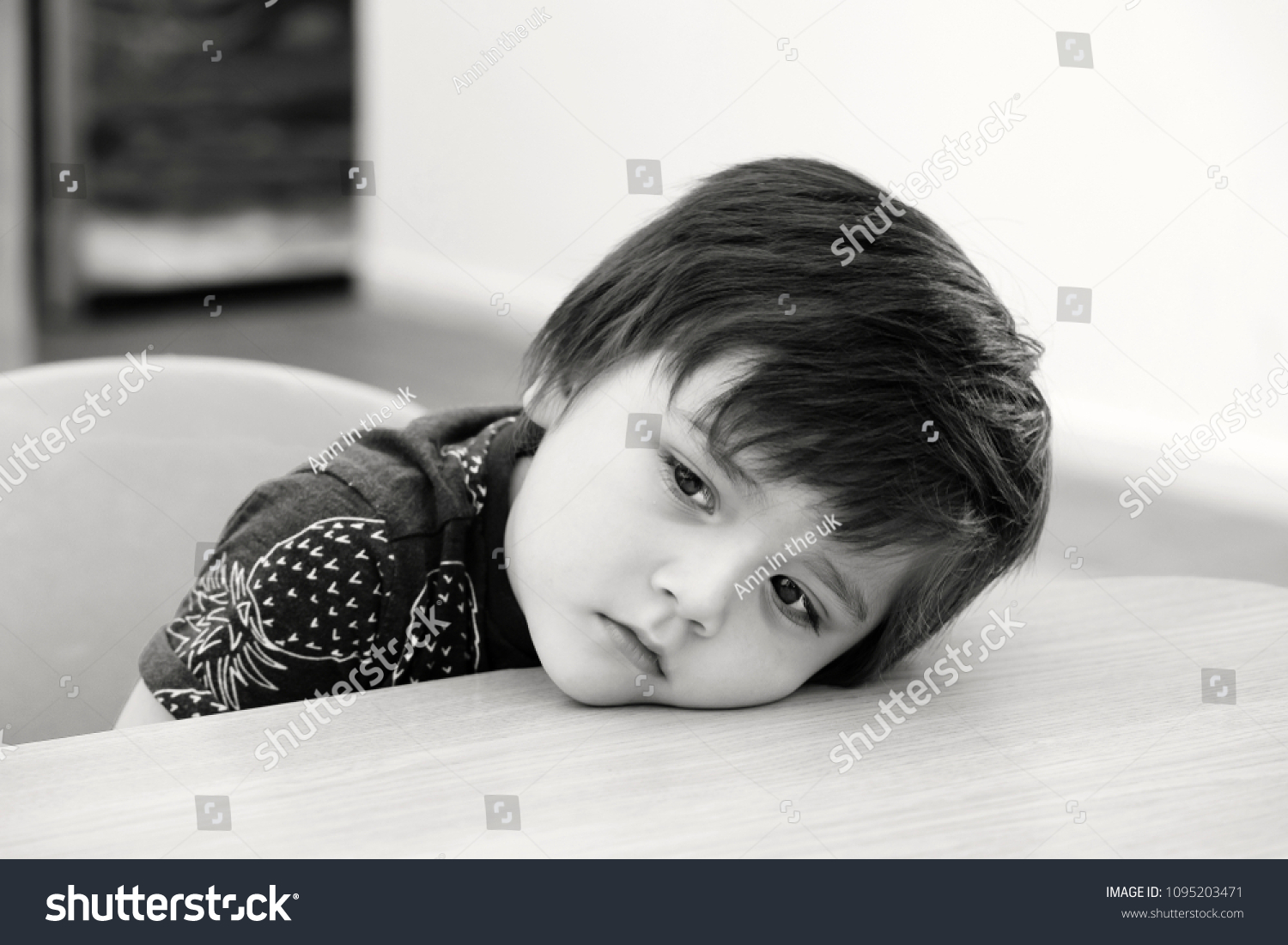 Black and white photo of lonely kid boy sitting alone putting head down with bored face