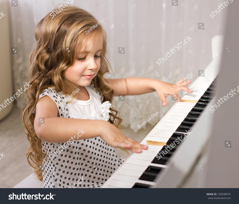 Beautiful Little Girl Playing Piano Light Stock Photo