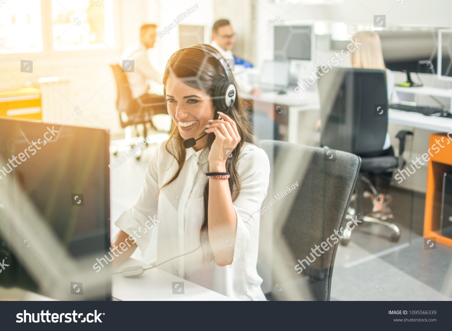 Smiling female customer support operator with headset working in office #1095566339