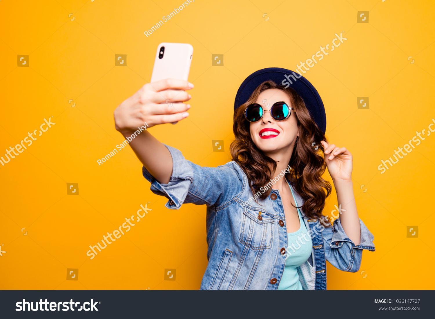 Portrait of cool cheerful girl having video-call with lover holding smart phone in hand shooting selfie on front camera isolated on yellow background enjoying weekend vacation #1096147727