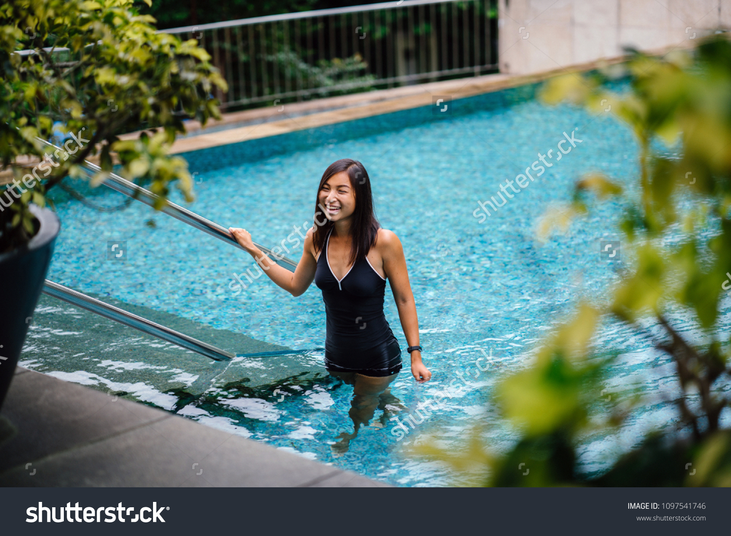 3f67500bc1a Portrait of a young Chinese Asian woman stepping out of the pool after a  refreshing swim