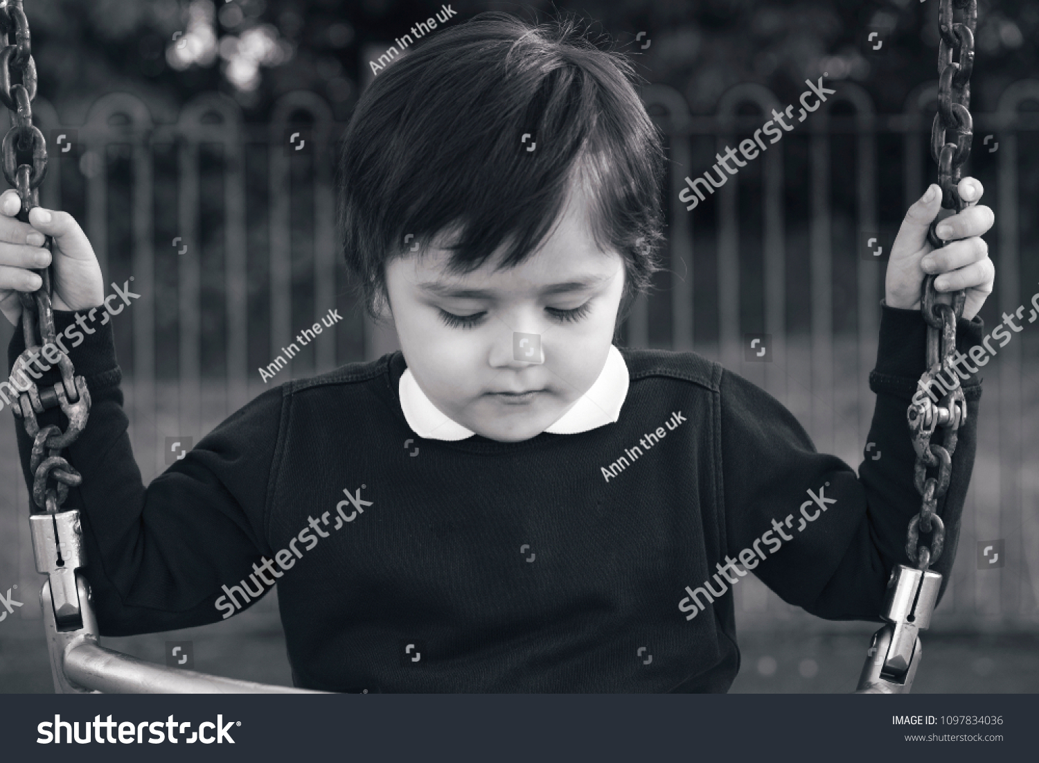 Lonely child with a sad face sitting alone on swing in the playground in black and