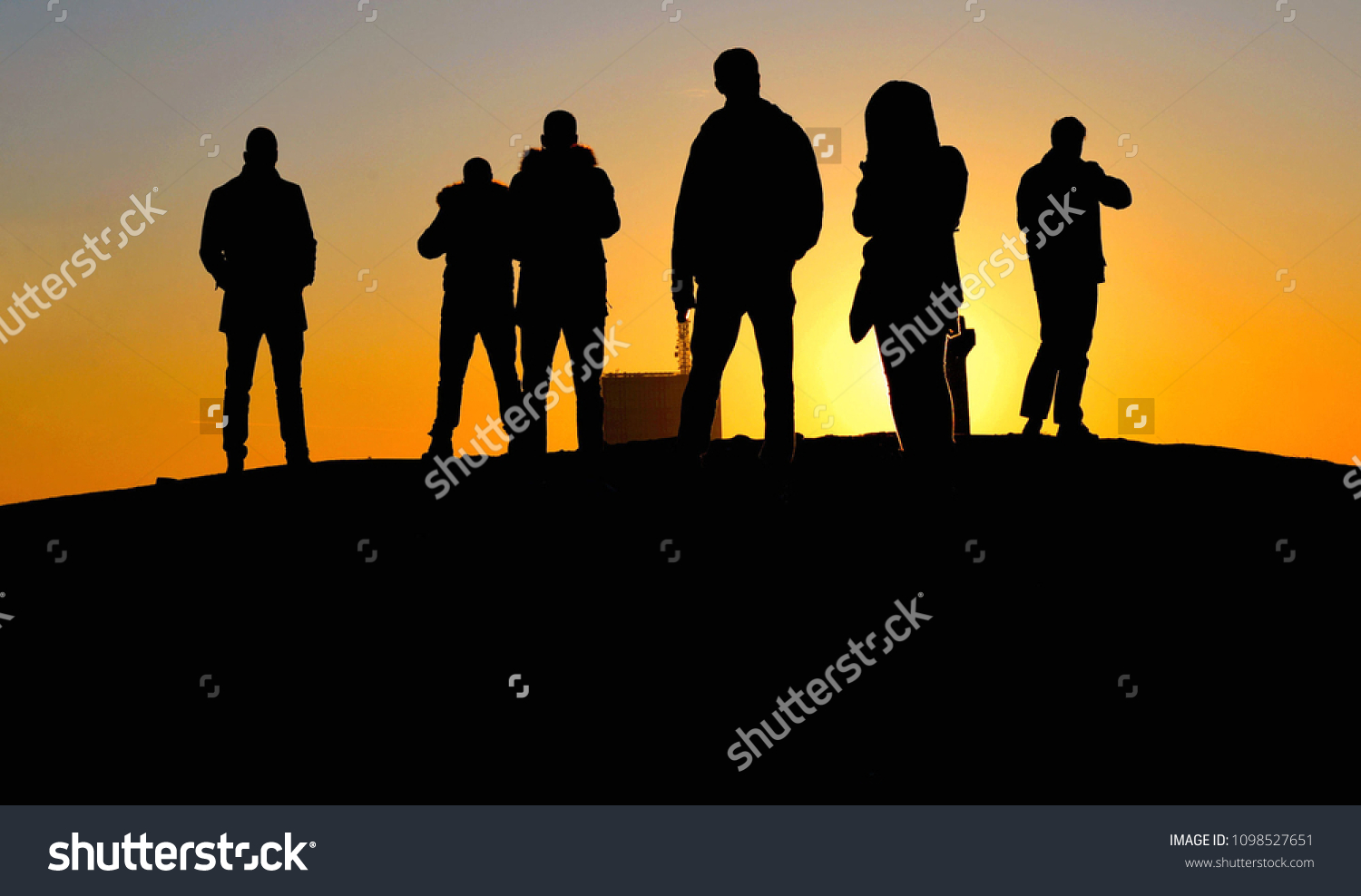 silhouettes of people on the hill with colorful warm orange sunset