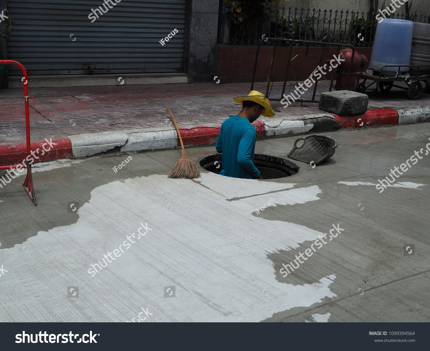 BANGKOK, THAILAND - MAY 27, 2018: A worker stands without personal protective equipment in a shallow manhole on May 27, 2018 in Bangkok, Thailand.