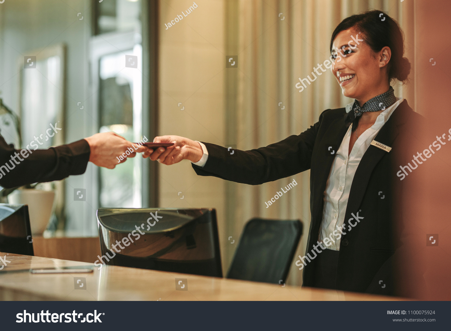 Smiling receptionist behind the hotel counter attending female guest. Concierge giving the documents to hotel guest. #1100075924