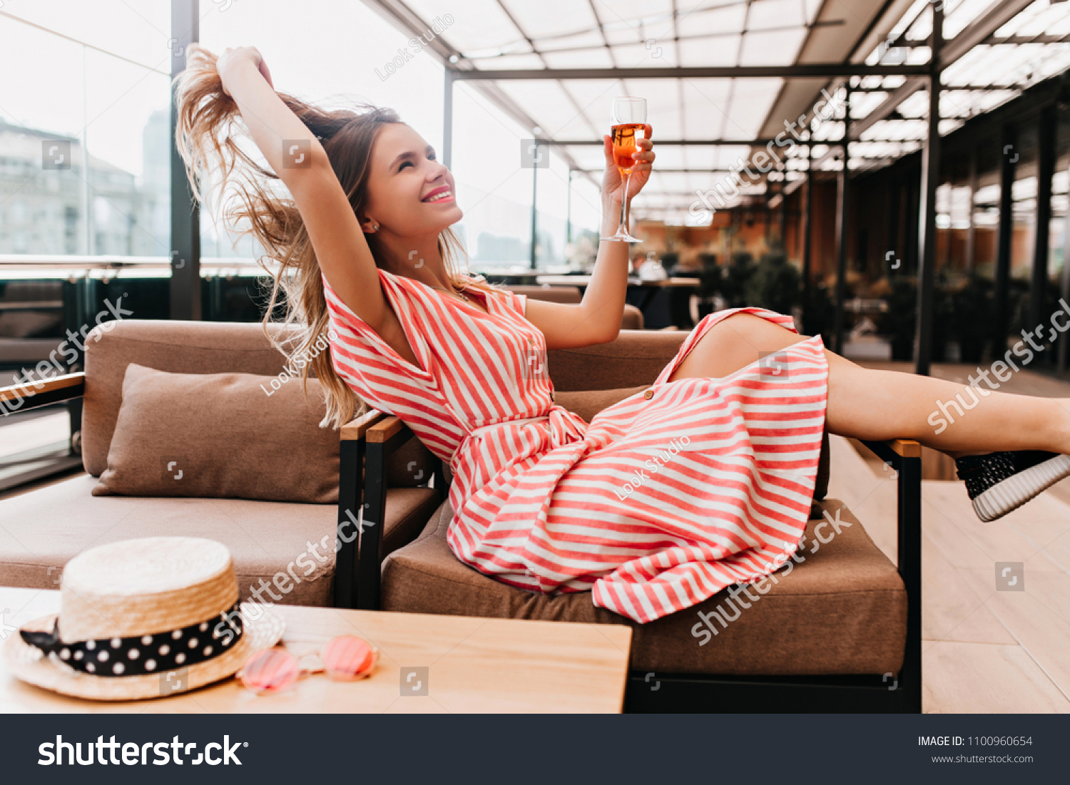 Ecstatic blonde girl playing with her hair while chilling in cafe. Inspired young woman in striped dress enjoying champagne in restaurant in summer weekend. #1100960654