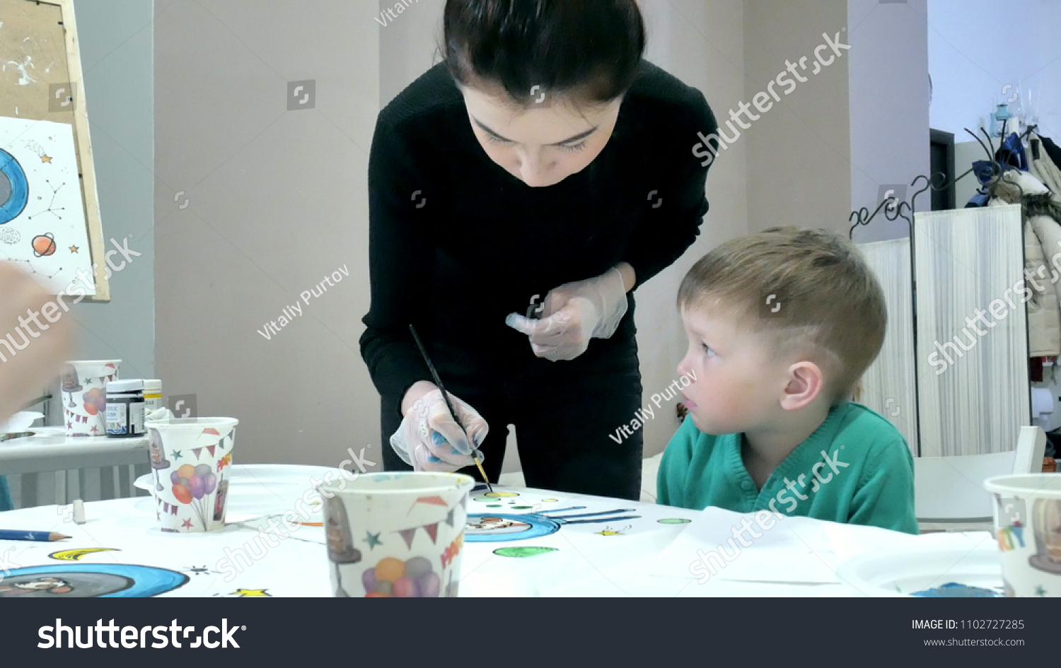 Children boys sitting together around the table in classroom and drawing.  With them is their