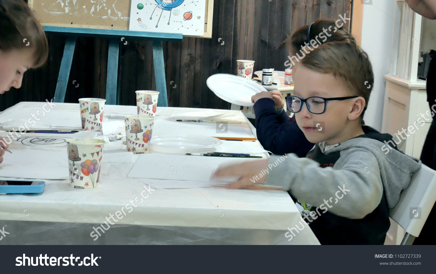 Children boys and girls sitting together around the table in classroom and  drawing. With them