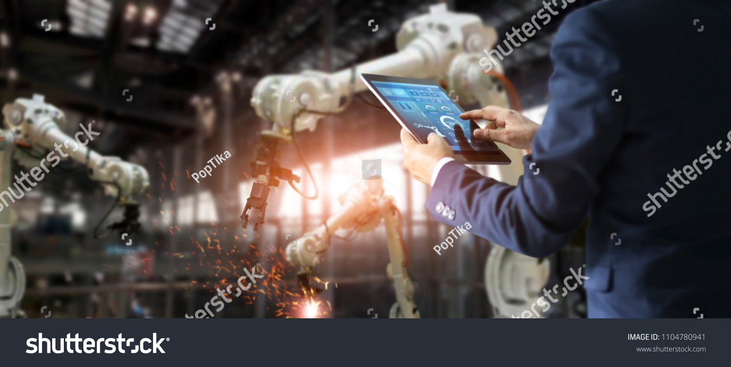 Manager engineer check and control automation robot arms machine in intelligent factory industrial on real time monitoring system software. Welding robotics and digital manufacturing operation.  #1104780941 - 123PhotoFree.com