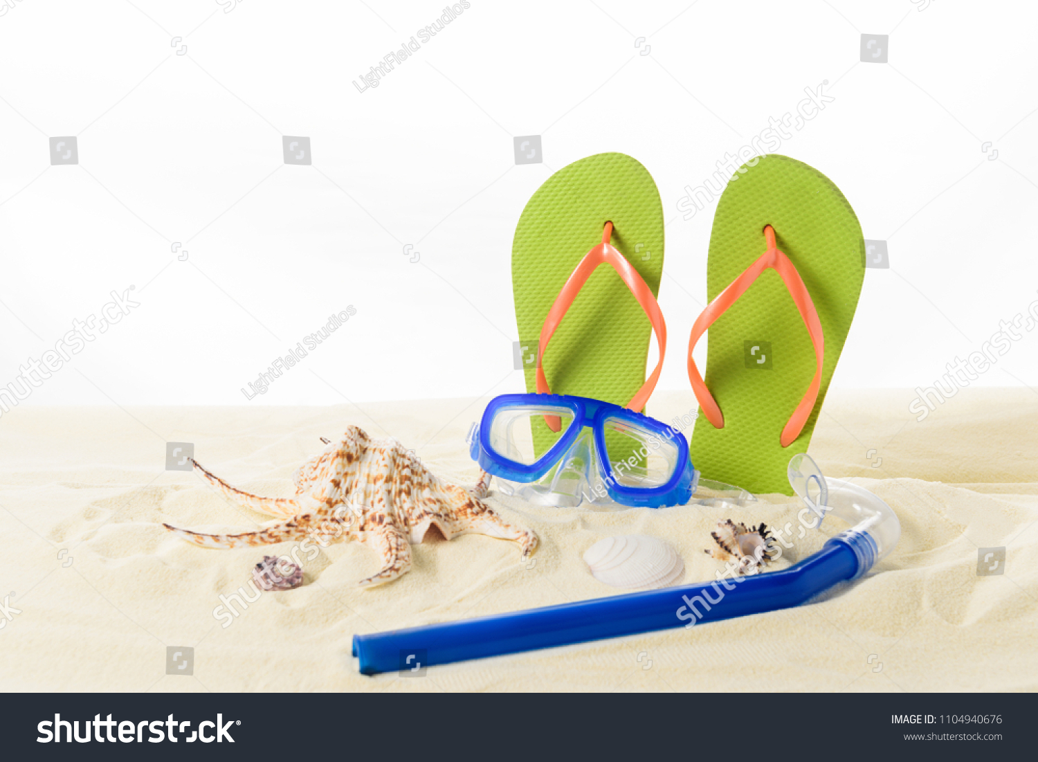 509d3fb63940 Flip flops and diving mask with seashells in sand isolated on white