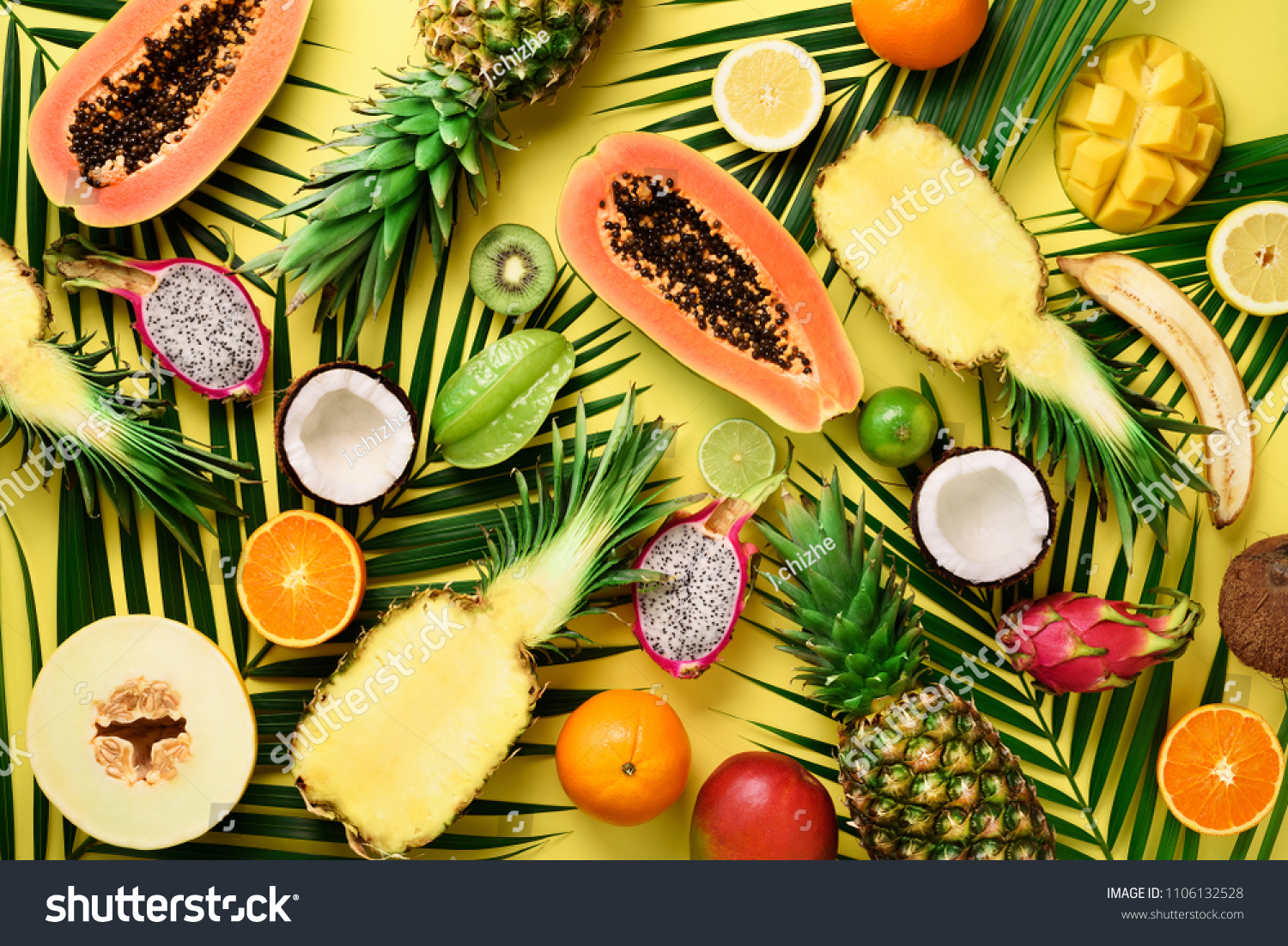 Exotic fruits and tropical palm leaves on pastel yellow background - papaya, mango, pineapple, banana, carambola, dragon fruit, kiwi, lemon, orange, melon, coconut, lime. Top view