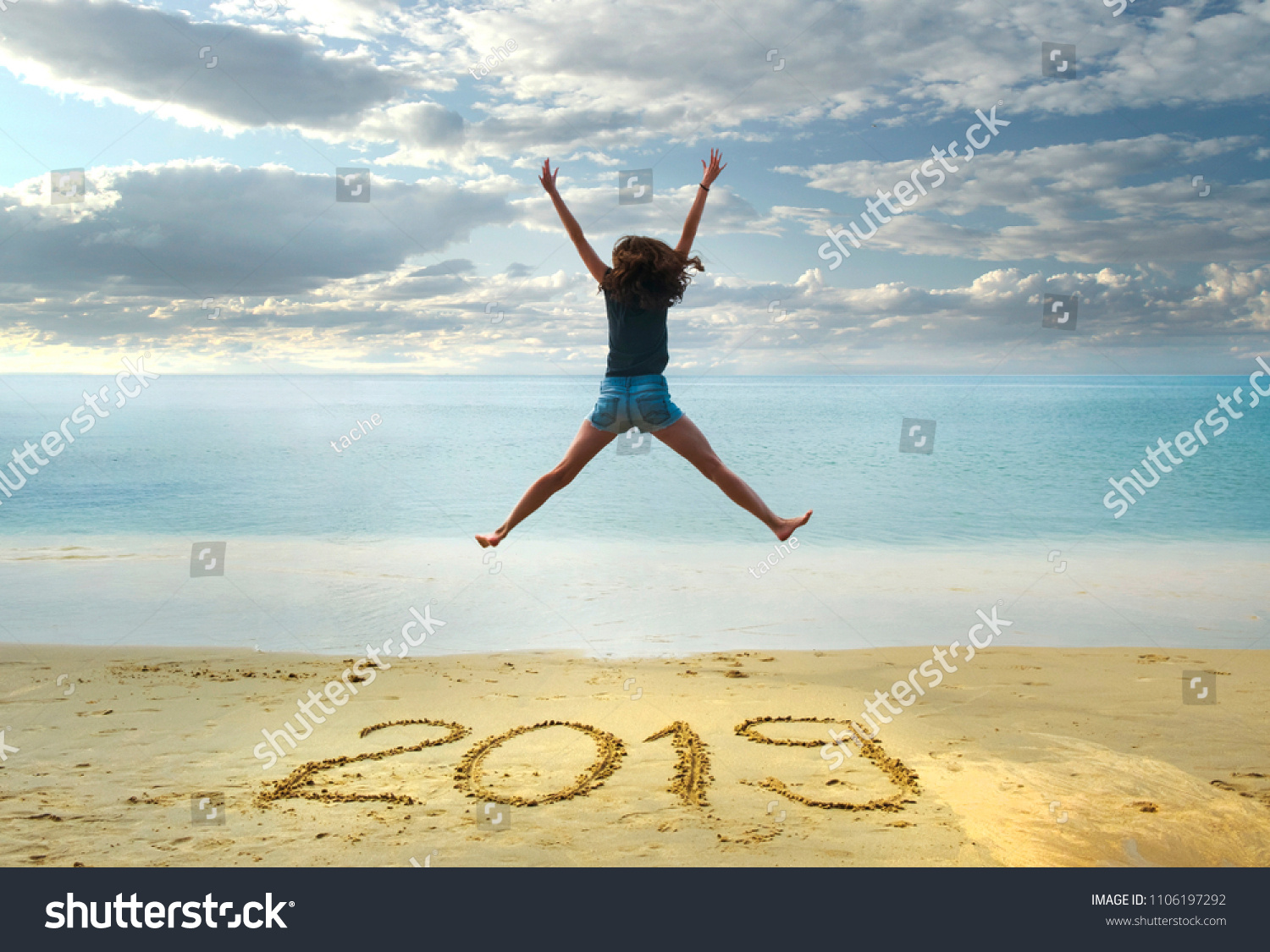 New Year 2019 on the sand,happy girl with hands up jumping on the beach #1106197292