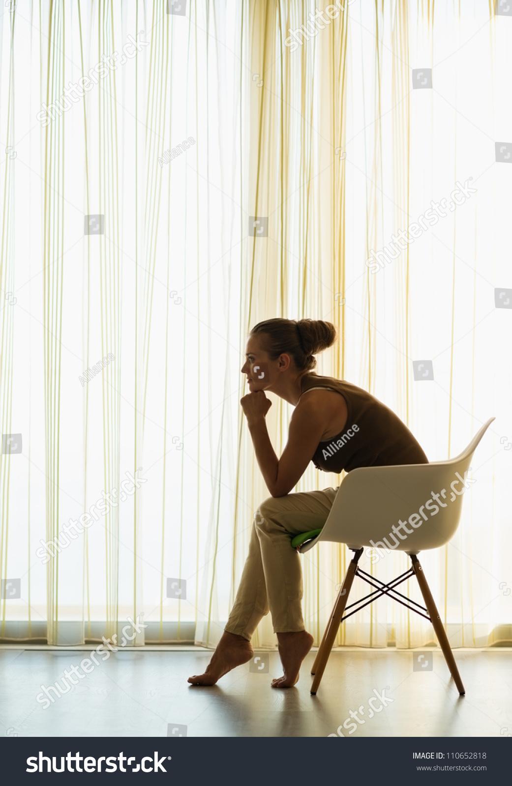 Woman Sitting Near Window Thoughtful Pose Stock Photo