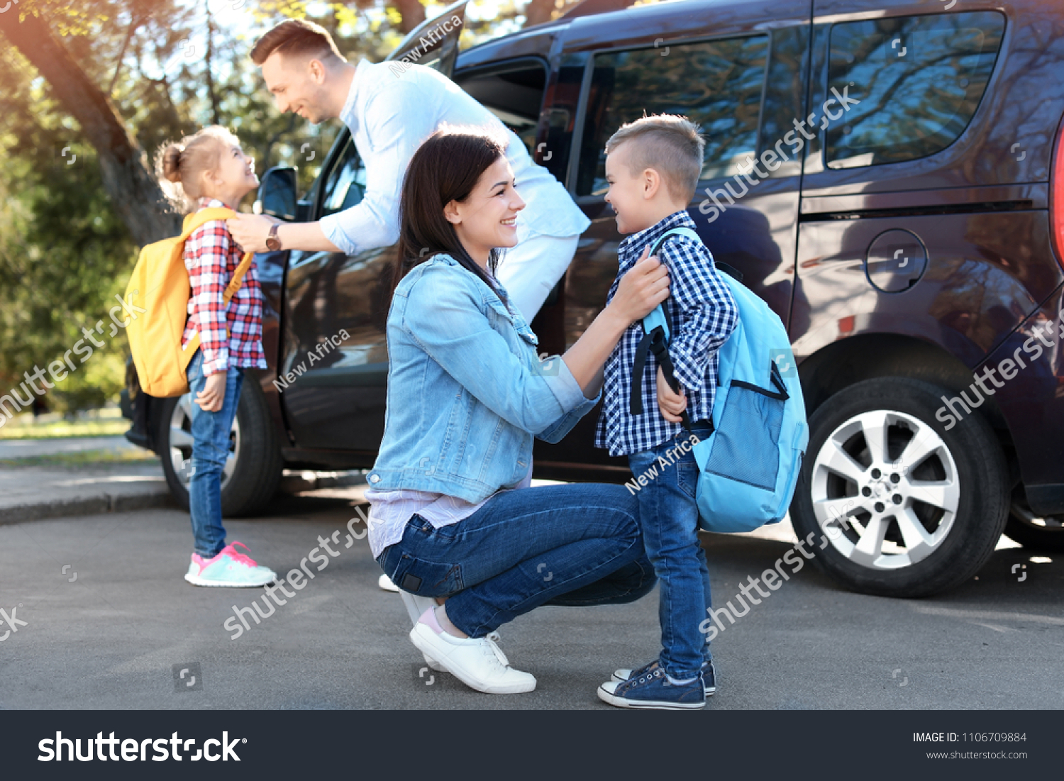 Young parents saying goodbye to their little children near school #1106709884