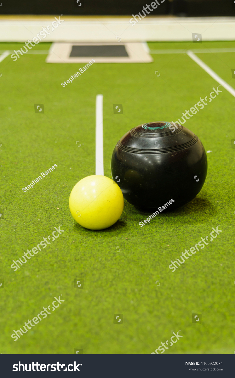 Bowl and jack on an indoor bowls carpet #1106922074