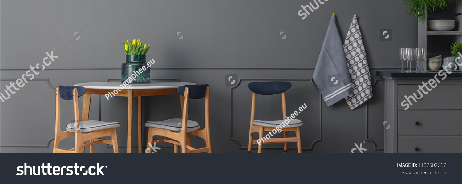 Grey, wooden chairs at round table against grey wall with molding in dining room interior #1107502667