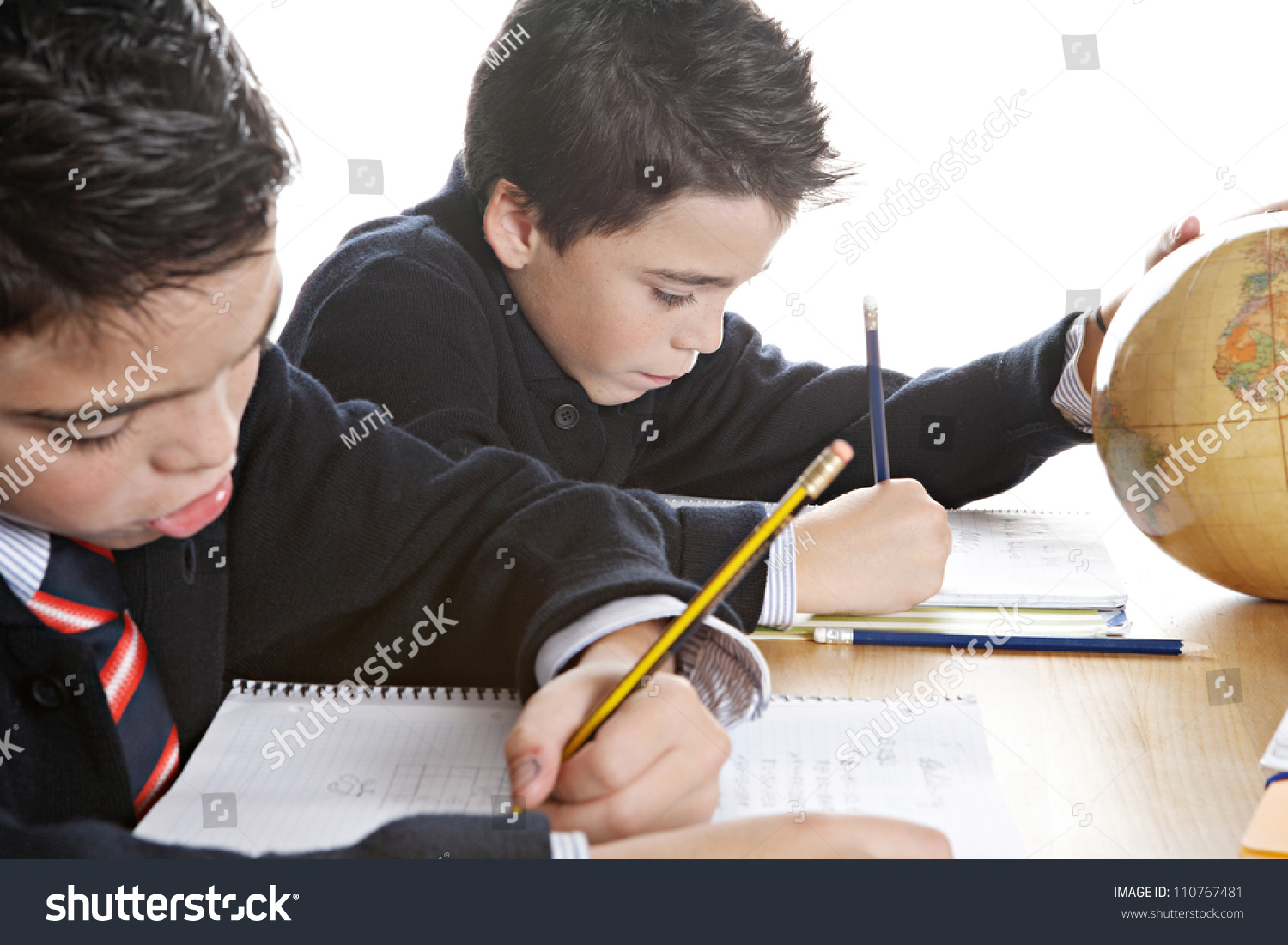 Two Identical Twin Brothers Doing Their Geography Homework