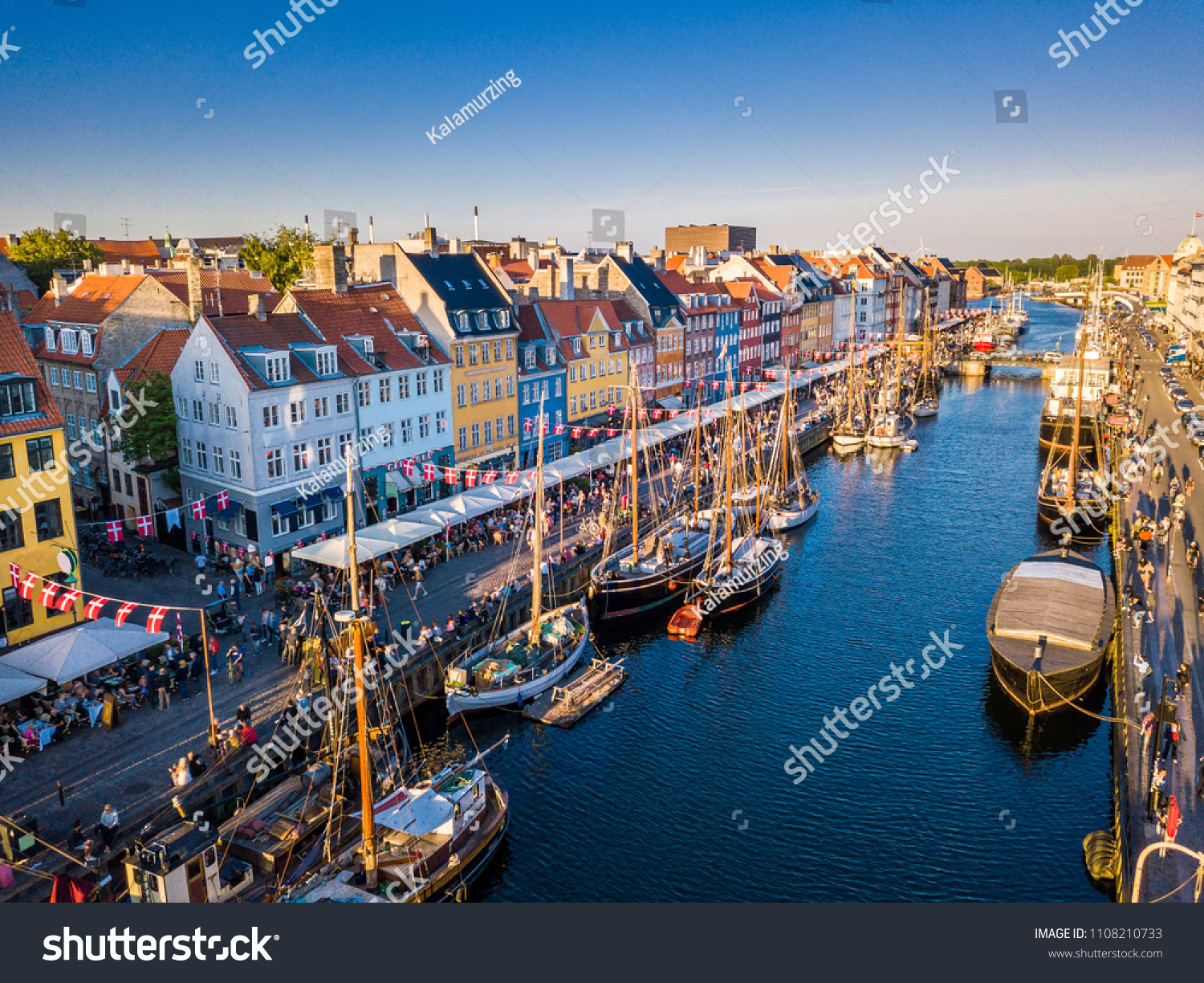 Beautiful historical city center. Nyhavn New Harbour canal and entertainment district in Copenhagen, Denmark. The canal harbours many historical wooden ships. Aerial view from the top. #1108210733