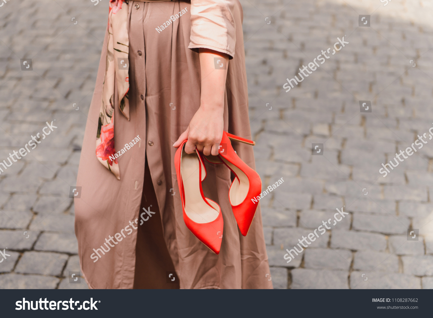 Elegant red high heels shoes in woman hands. Girl wearing beige trench coat standing on a stony pavement, holding her trendy, fashion footwear in hands #1108287662