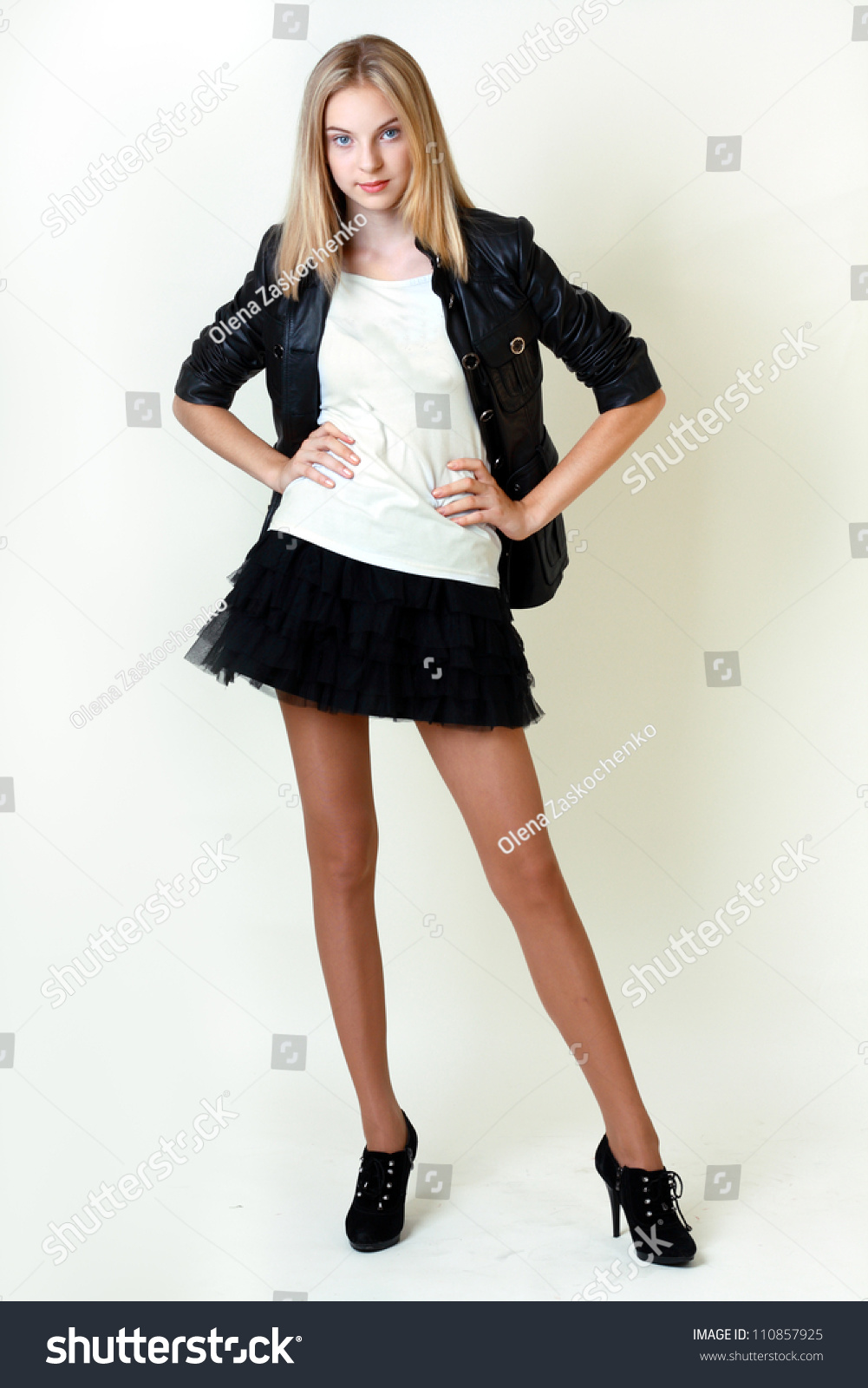 d3a537f25 Portrait of trendy teen girl in miniskirt and leather jacket smiling against  white background