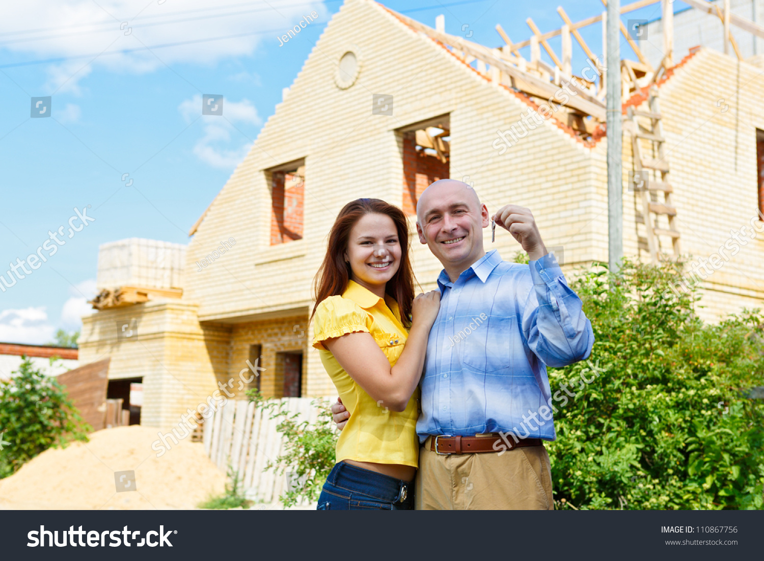 Happy smiling young couple showing a pair of keys of their new house stock photo 110867756 - Young couple modern homes ...