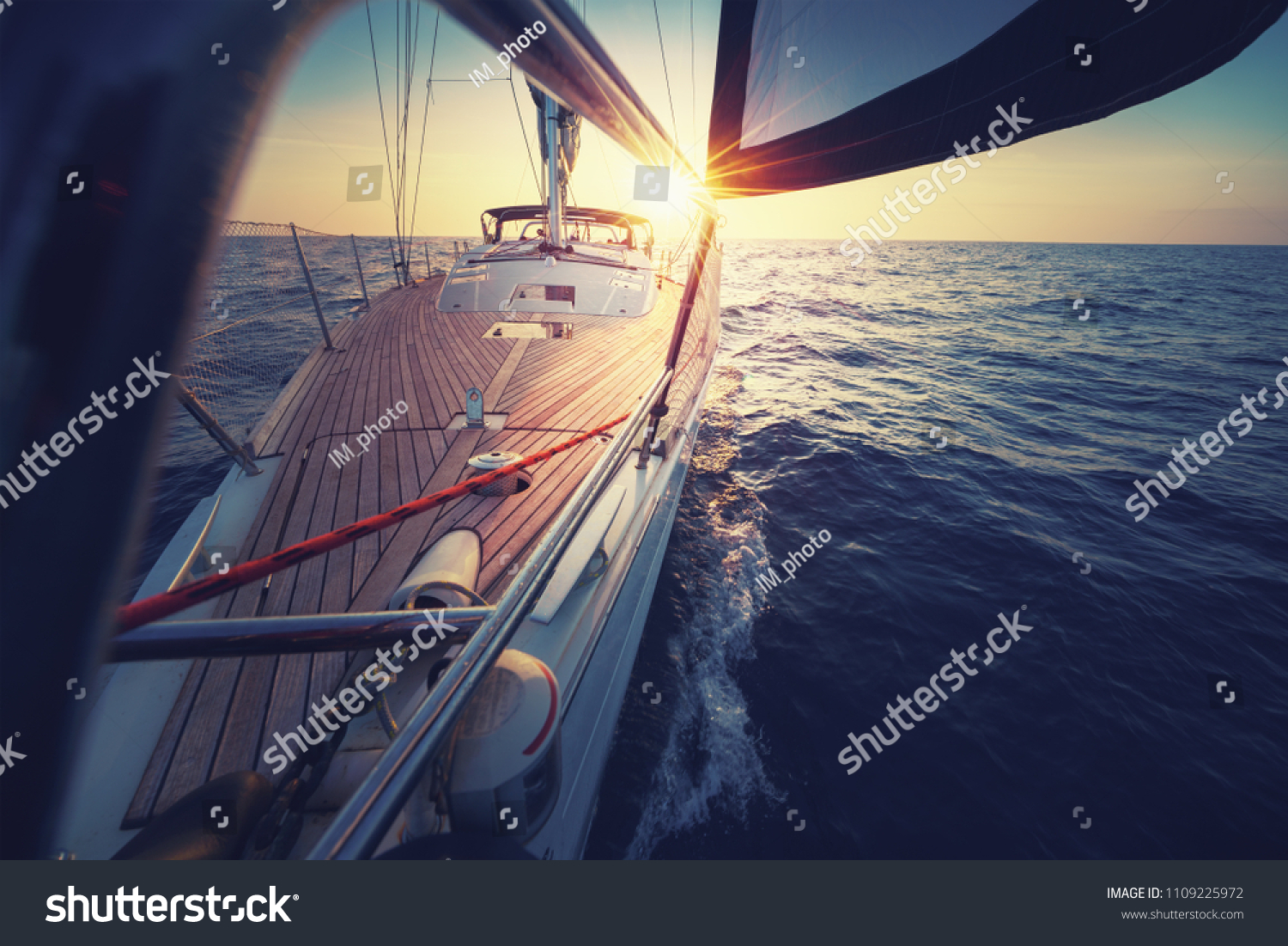 Sunset at the Sailboat deck while cruising / sailing at opened sea. Yacht with full sails up at the end of windy day. Sailing theme - background. Yachting background design. #1109225972