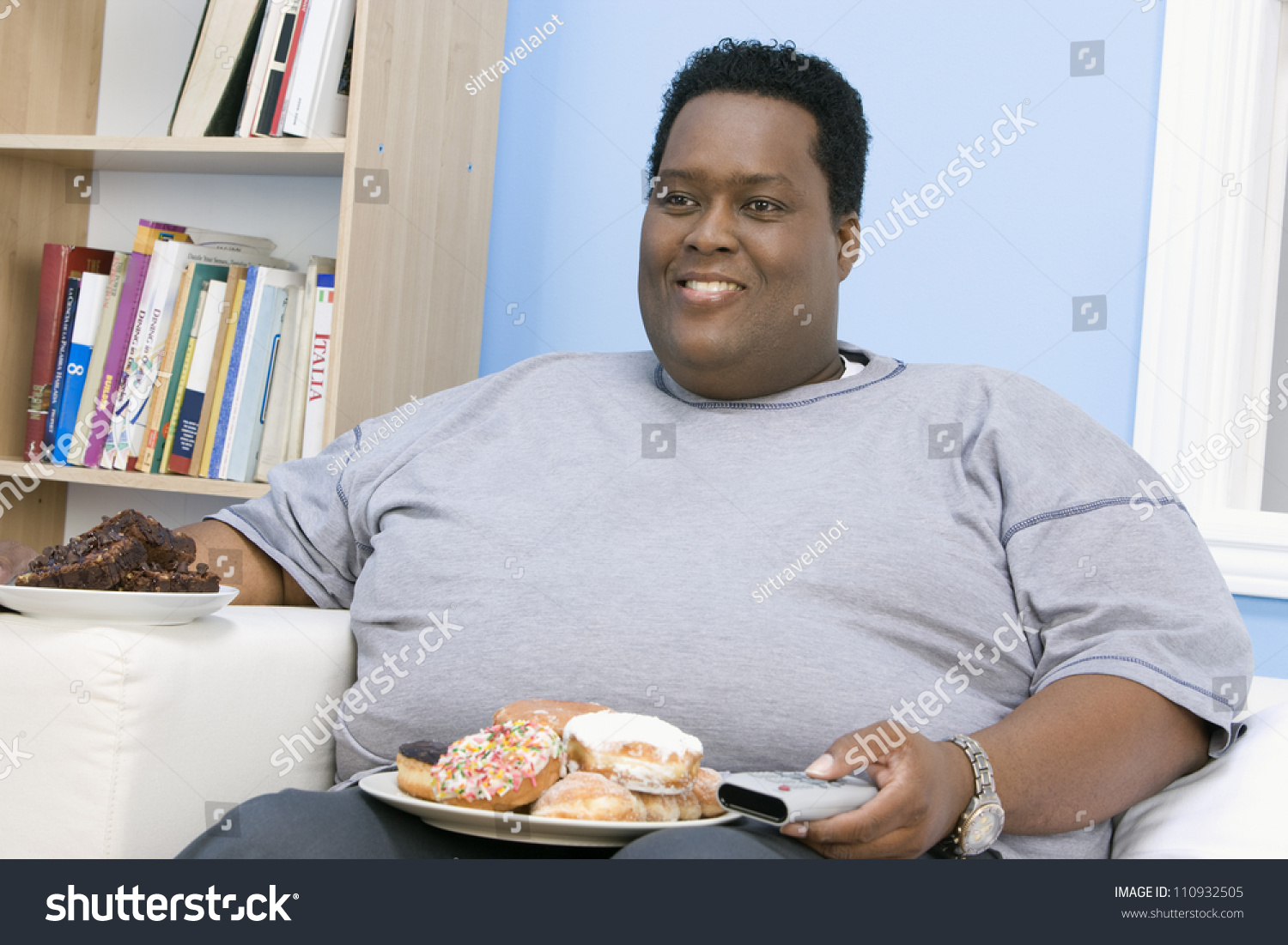 stock-photo-african-american-man-eating-donut-while-watching-television-110932505.jpg
