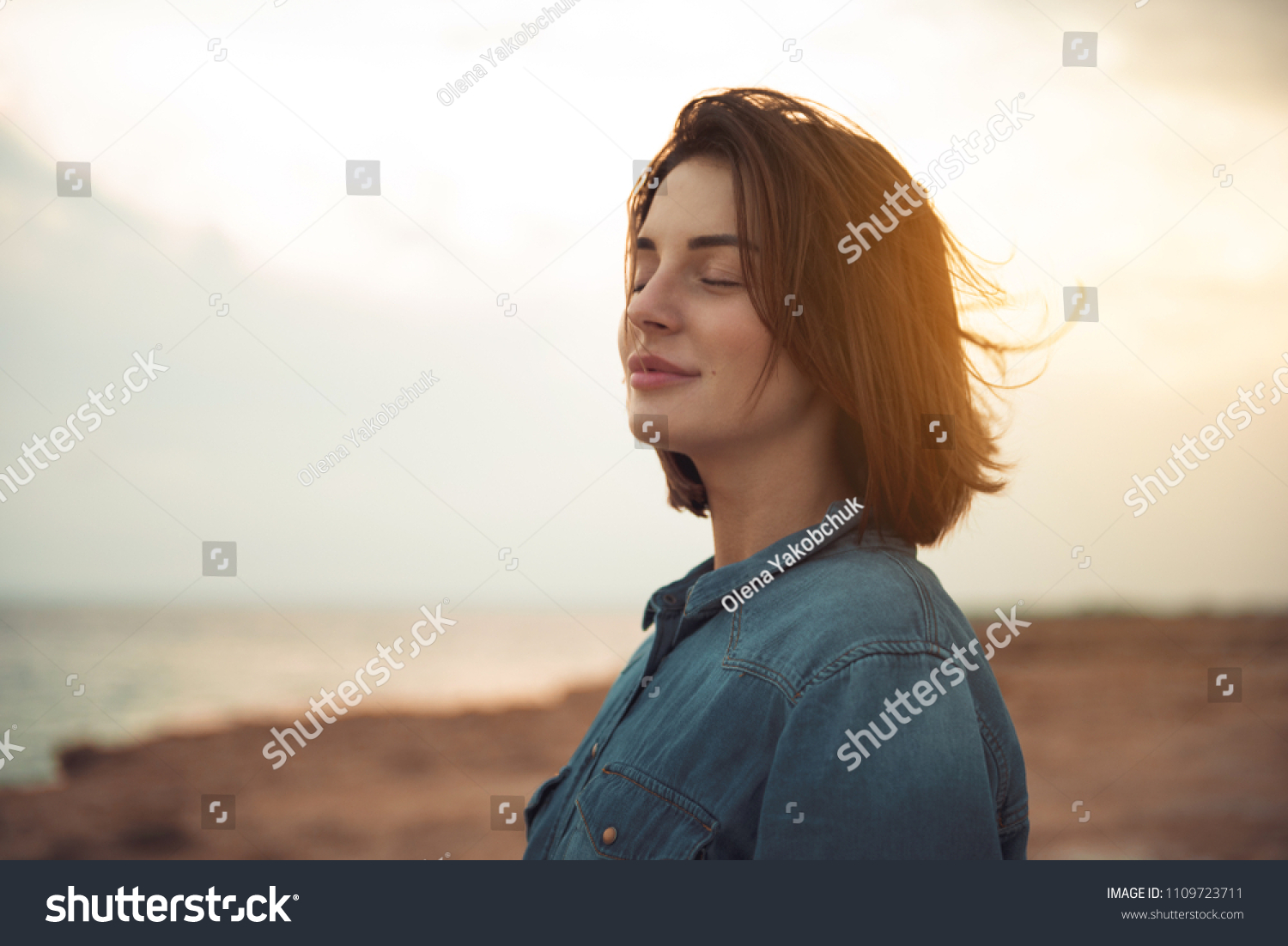 Great pleasure. Charming calm young woman is standing near sea with closed eyes and expressing delight. She is posing against wonderful sunset while enjoying last rays of the sun #1109723711