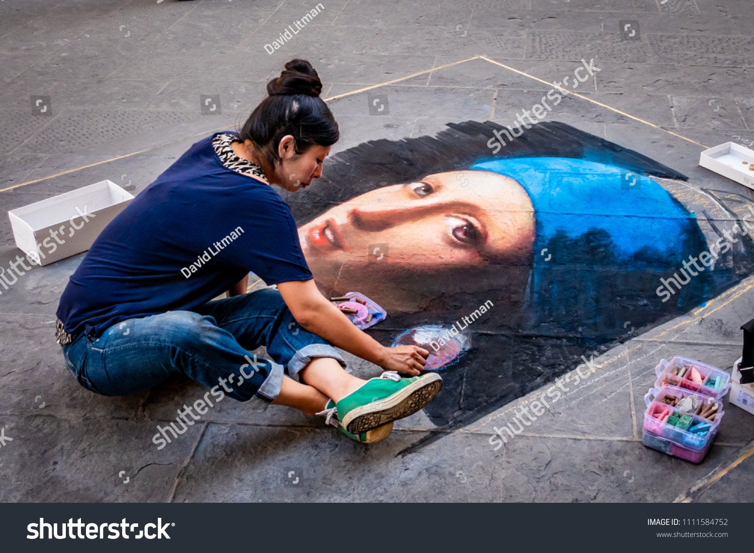 Florence, Italy - June 7, 2018: An artist draws a beautiful sidewalk mural in renaissance style with colorful chalk.