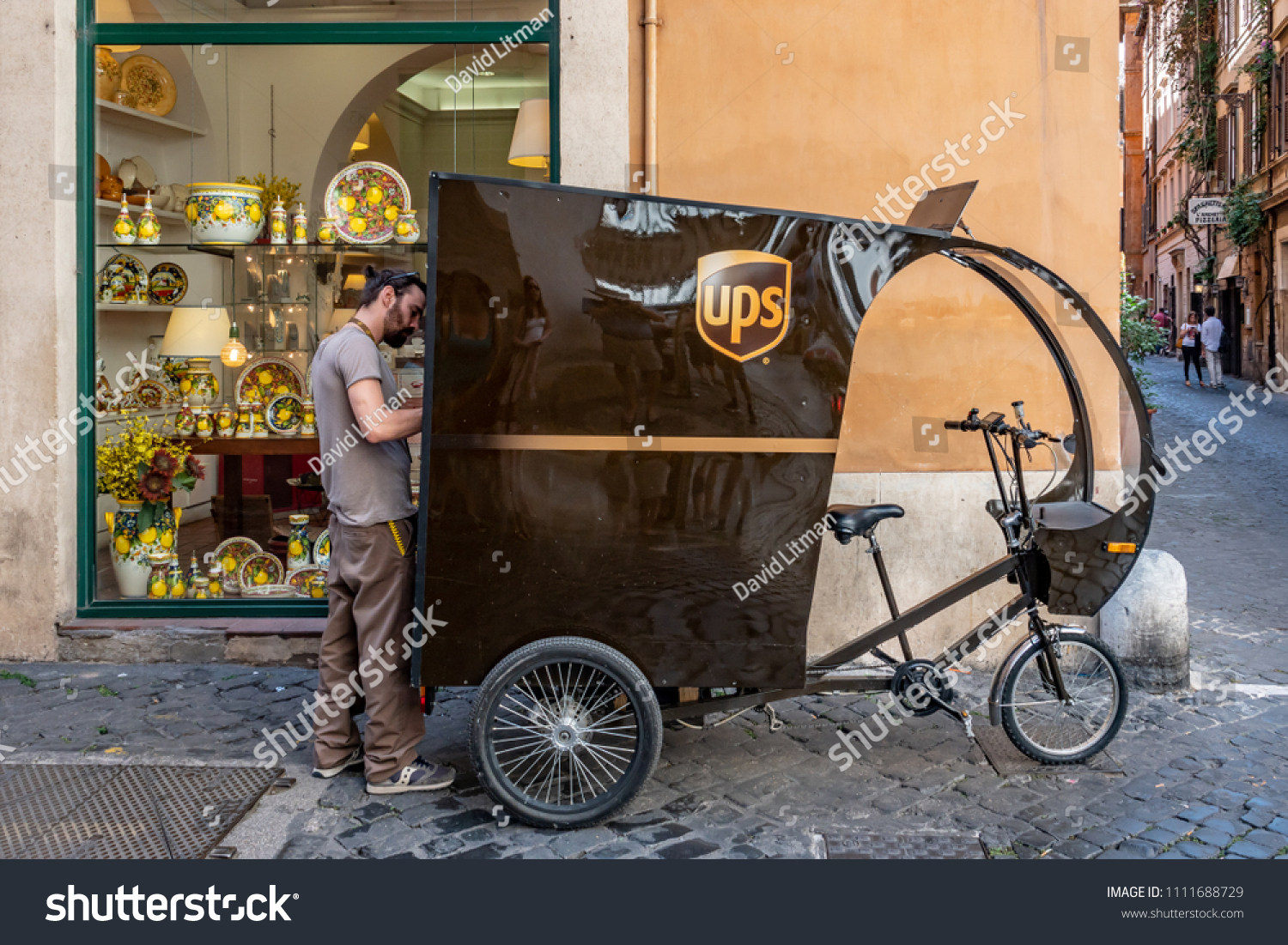 Rome, Italy - June 5, 2018: A UPS delivery man delivers packages using a peddle driven cargo tricycle through the narrow streets of Rome.