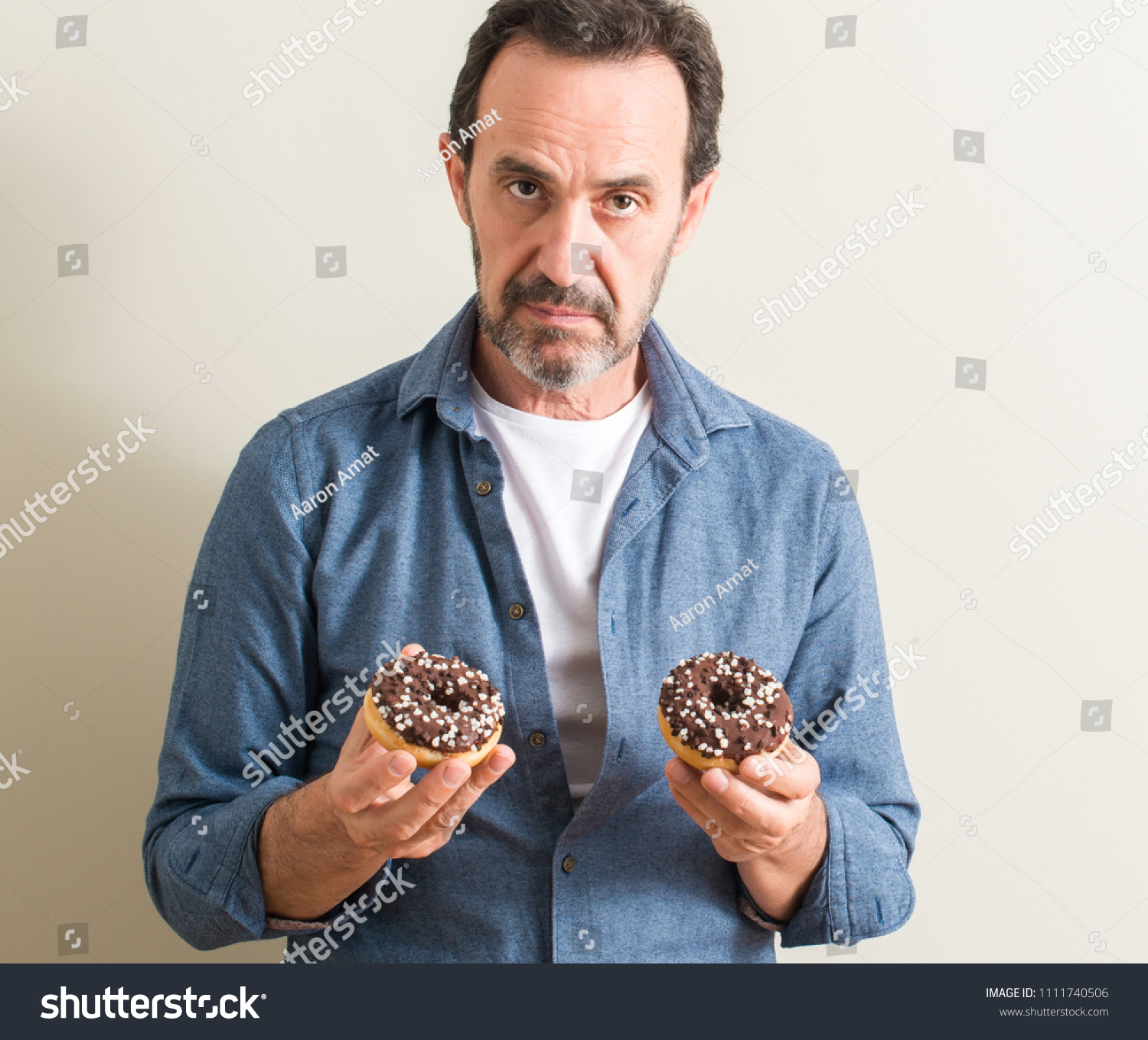 716783cab1e Senior man eating chocolate donut with a confident expression on smart face  thinking serious