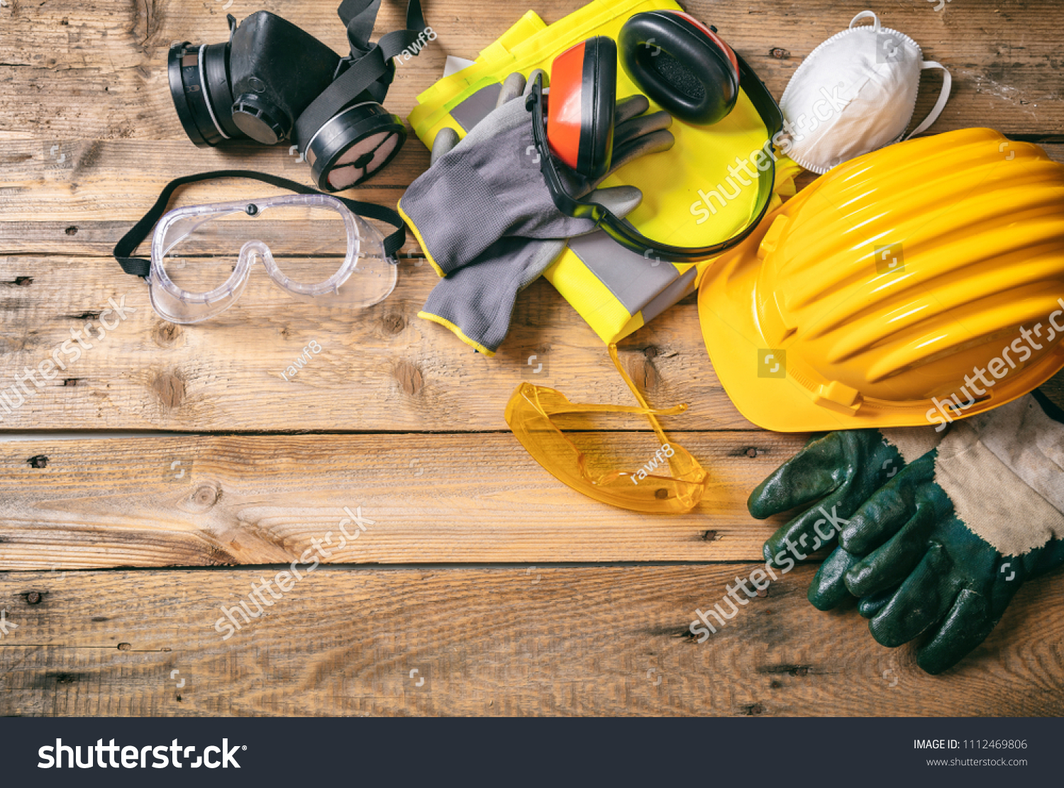 Work safety. Construction site protective equipment on wooden background, flat lay, copy space, top view #1112469806