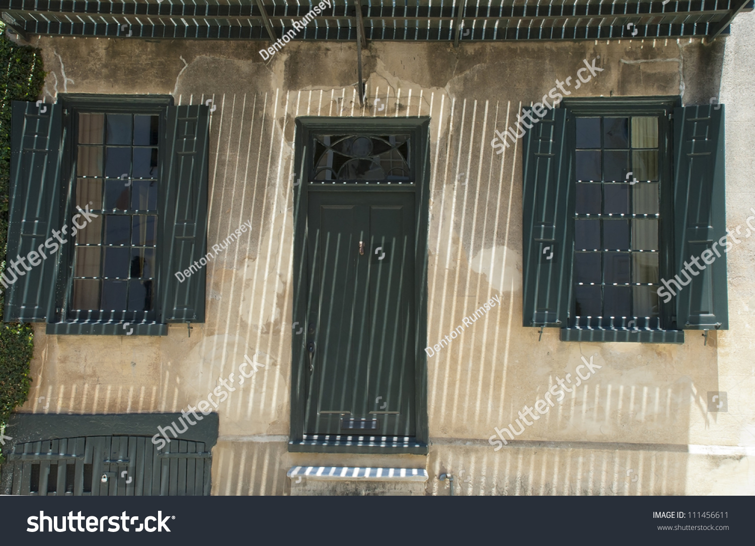 The iron bars of a balcony cast a grilled patterned shadow over the front door of & Iron Bars Balcony Cast Grilled Patterned Stock Photo (Royalty Free ...