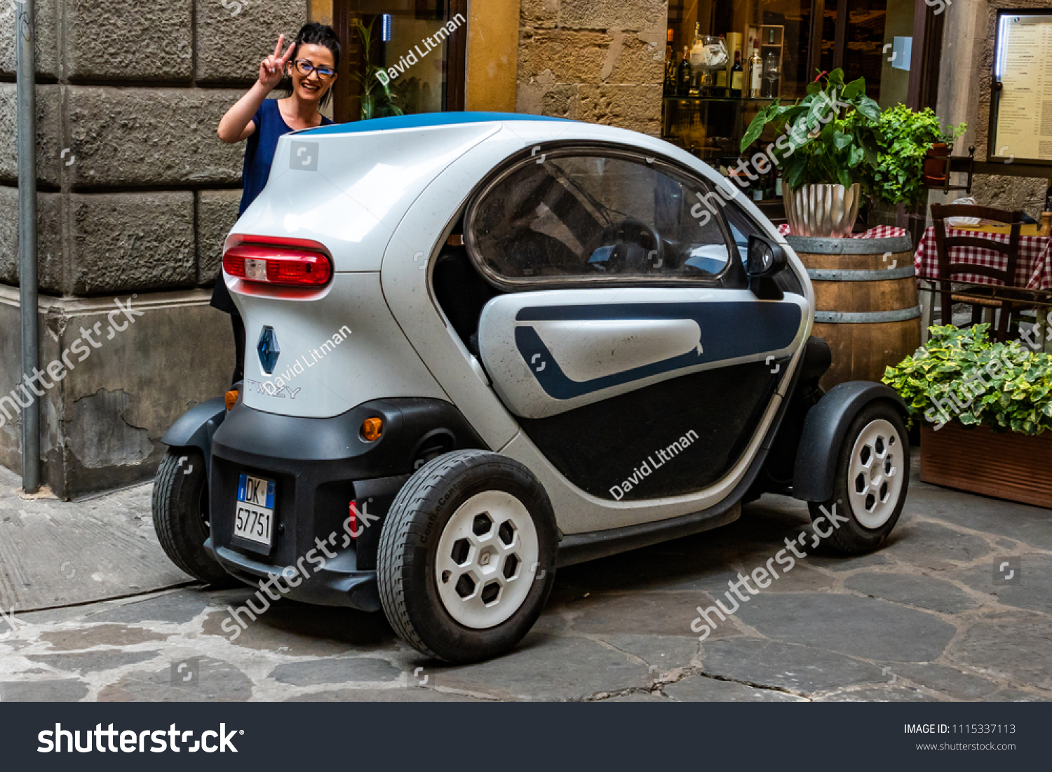 Florence, Italy - June 8, 2018: A woman shows off her Twizy, a small two-seat electric car designed and marketed by Renault and manufactured in Valladolid, Spain.