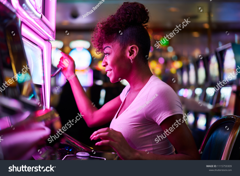 happy woman gambling at casino playing slot machine #1115759309