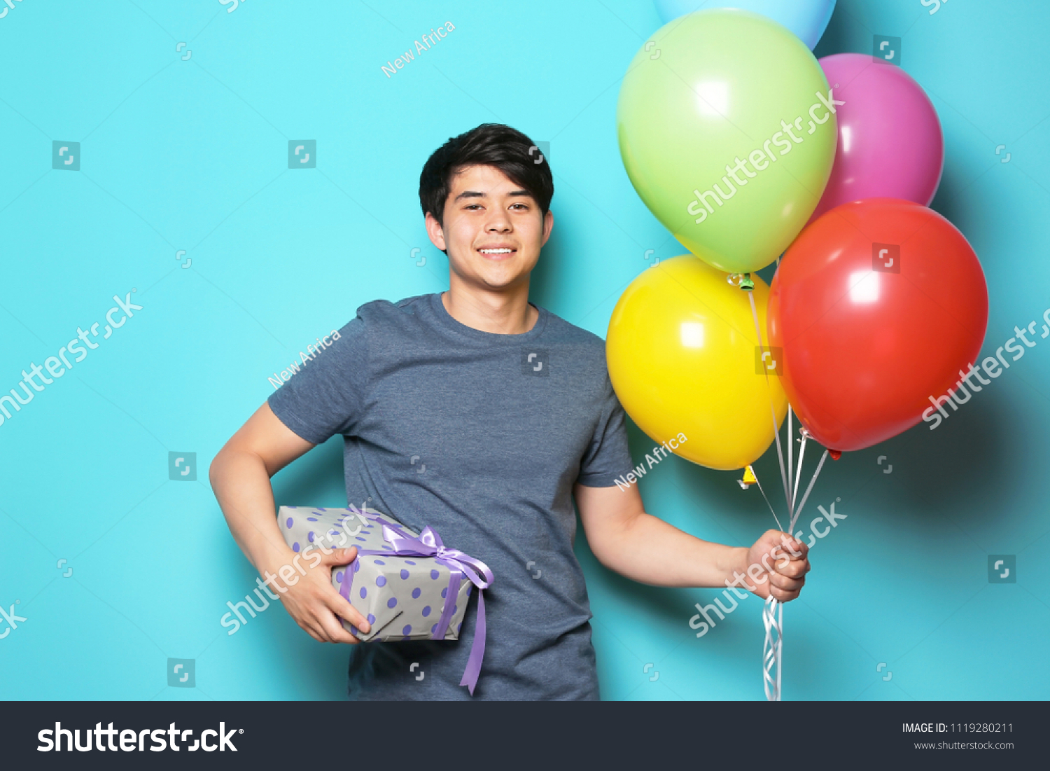 Young Man With Bright Balloons And Birthday Gift On Color Background