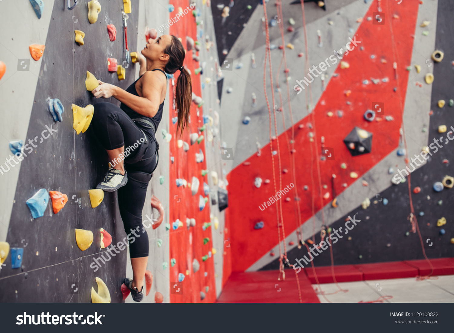 Rear view of sportwoman climber moving up on steep rock, climbing on artificial wall indoors. Extreme sports and bouldering concept.